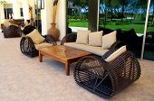 stock photo of settee  - wicker outdoor furnitures on terrace of summer luxury resort - JPG