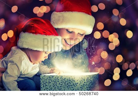 Christmas Magic Gift Box And A Happy Family Mother And Baby poster