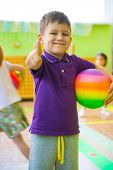 image of daycare  - Cute little boy playing at daycare gym with ball - JPG