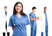 stock photo of nurse uniform  - Portrait of a beautiful smiling nurse in front of her medical team - JPG
