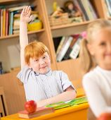 Little redhead schoolboy behind school desk during lesson with his hand up