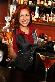 stock photo of redheaded  - Beautiful redhead barmaid with bottle behind bar counter - JPG