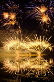 stock photo of guy fawks  - Golden and Purple Fireworks reflected in a murky lake - JPG