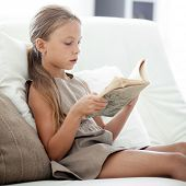 Portrait of 7 years old child reading book on the sofa at home