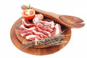 raw beef asado ribs with thyme and tomatoes on wooden board isolated over white background