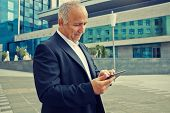 senior businessman using touchpad at outdoor