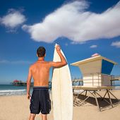 Boy surfer back rear view holding surfboard on Huntington beach lifeguard house [ photo-illustration
