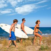 Surfer teen boys and girl group walking on dune way to beach on summer