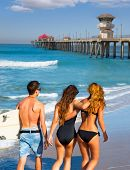 Teen surfers group of boys and girls walking rear view on Huntington beach California [ photo-illust