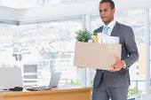 Sad businessman leaving his company while he is holding a box