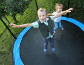 stock photo of playground school  - Two funny kids jumping on a outdoor trampoline - JPG