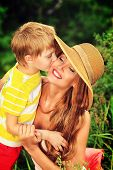 Happy son kisses his beloved mother. Outdoor.