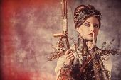 image of post-apocalypse  - Portrait of a beautiful steampunk woman holding a gun over grunge background - JPG