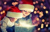 stock photo of christmas hat  - Christmas magic gift box and a woman happy family mother and Child baby - JPG