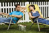 Couple relaxing in lawn chairs