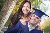 Happy Male Graduate in Cap and Gown and Pretty Girl Celebrate Outside.