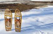 classic wooden Bear Paw snowshoes on the shore of partially frozen Cache la Poudre River near Fort Collins, Colorado
