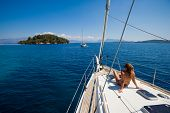 stock photo of yachts  - Young woman Sailing On Yacht in Greece - JPG