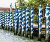 Blue And White Gondola Poles In Venice Canal