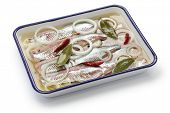 pickled herring on white enamel tray