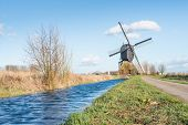 foto of water-mill  - Historic windmill in a rural landscape with a narrow ditch with a very high water level at the end of the winter season in the Netherlands - JPG