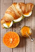 pic of croissant  - Croissant sandwich with egg orange fruit and marmalade for breakfast on a wooden board.