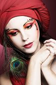 stock photo of turban  - Portrait of young woman in red turban with peacock plume - JPG