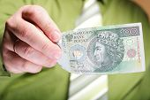 picture of zloty  - Businessman holding polish money hundred zloty banknote - JPG