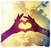 picture of love making  -  two hands making a heart shape in the sky done with a vintage retro instagram filter - JPG