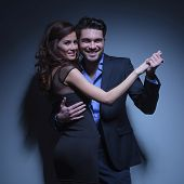 portrait of a young fashion couple smiling while standing in a dance pose and looking into the camera. on a dark blue background