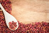 Raw red beans and a spoon framing a wooden background with space for text