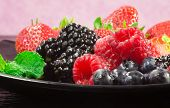 stock photo of greedy  - greedy red fruits close up over pink background - JPG