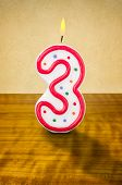 Burning birthday candle number 3 on a wooden background