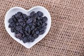 pic of barberry  - Barberry in cup in the shape of heart on sack cloth - JPG