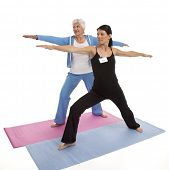 "Female yoga instructor teaching ""Warrior"" position to senior adult woman on white background."