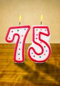Burning birthday candles number 75 on a wooden background