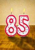Burning birthday candles number 85 on a wooden background