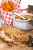 Delicious panini made with ham, pork and swiss cheese served with a vegetable soup, pickles and swee