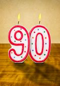Burning birthday candles number 90 on a wooden background