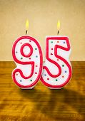Burning birthday candles number 95 on a wooden background