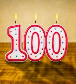 Burning birthday candles number 100 on a wooden background