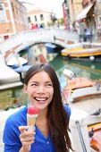 Ice cream eating woman in Venice, Italy on vacation travel. Smiling happy young asian woman tourist