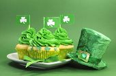 stock photo of leprechaun hat  - Happy St Patricks Day green cupcakes with shamrock flags and leprechaun hat against a green background - JPG