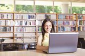 Female student working with laptop in a high school library