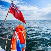 Blue Sea. View From Deck Of Yacht Sailboat British Flag Lifebuoy. Travel.