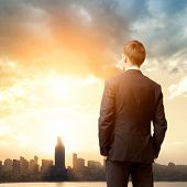 stock photo of sunrise  - business man look sunrise in the city - JPG