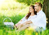 Beautiful Young Couple Having Picnic in Countryside. Happy Family Outdoor. Smiling Man and Woman relaxing in Park. Relationships