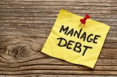 manage debt - yellow reminder note against grained wood board