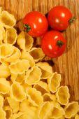 Macaroni and tomato on wooden background
