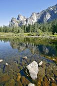 The magnificent Yosemite Valley. The mirror surface of the Merced river reflects the picturesque cliff tops and blue sky
